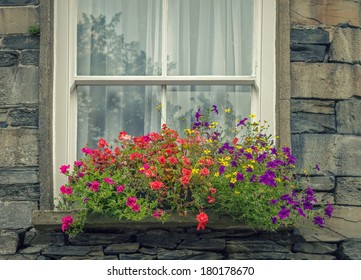 Colourful Flowers in a Window Box of an Old English Stone House.