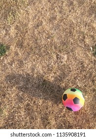 A colourful football on some dry grass