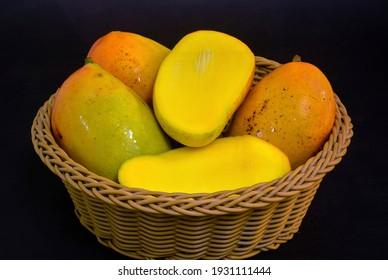 Colourful fresh ripe sliced and whole mango on basket.