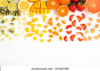 Colourful fruit balloon in rainbow colours top view on the white background: strawberries, blueberries, mango, orange, kiwis