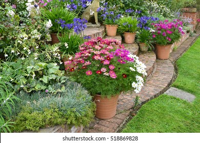 Colourful garden terrace with mixed flower beds and planted containers making a very attractice display in fronr of a country house