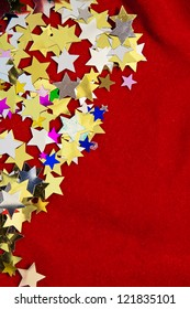 Colourful, glittering stars on gold background. Christmas wishes or birthday message. Plenty of copy space, portrait orientation.