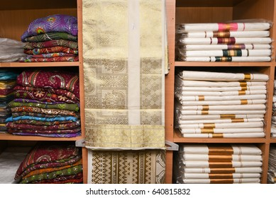 Colourful hand embroidered traditional designer saree, Kerala sari with thread work made of cotton and silk arranged in a shelf for sale, Kerala, Rajasthan, India. Ethnic clothing of Indian woman.