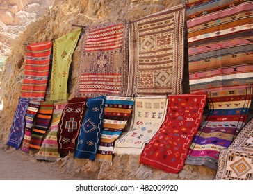 Colourful hand woven woollen rugs displayed for sale at Todgha Gorge in Morocco.