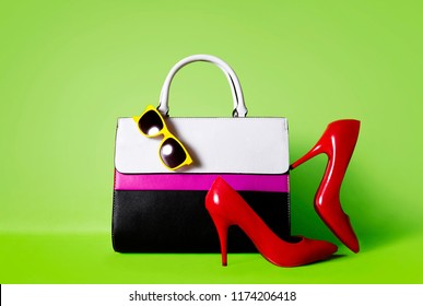 Colourful handbag, red heels, and yellow sunglasses isolated on green background. Woman shopping image.