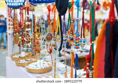 Colourful handicrafts, mostly womens' costume jewellery items hanging for retail display inside a craft store. Shot at Saras Mela, a craft fair to showcase West Bengal's handicraft, organised annually