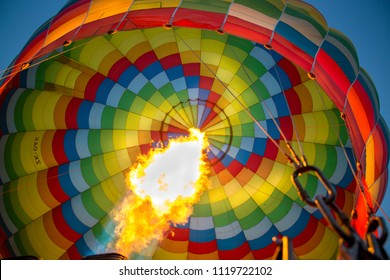A colourful hot air balloon is inflated with hot gas before taking off