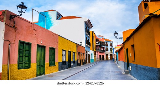 Colourful houses on street in Puerto de la Cruz town, Tenerife, Canary Islands, Spain. This is tourist pedestrian street near the ocean there are many restaurants and stores