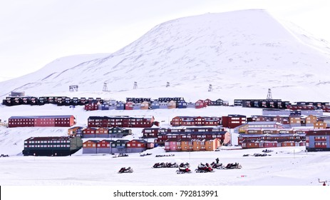 The colourful houses of the town of Longyearbyen, the largest settlement and the administrative center of Svalbard, Norway, the city panoramic view at the clear sunny spring day with rocks on the back