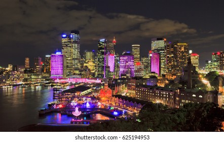 Colourful illuminated city of Sydney - high-rises at light show night from elevated Harbour bridge pylon lookout.