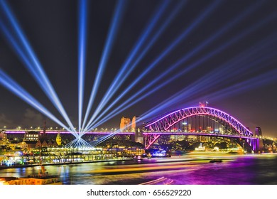Colourful illumination of Sydney Harbour bridge and overseas passenger terminal around Circular Quay and The Rocks during Vivid Sydney light show and festival.