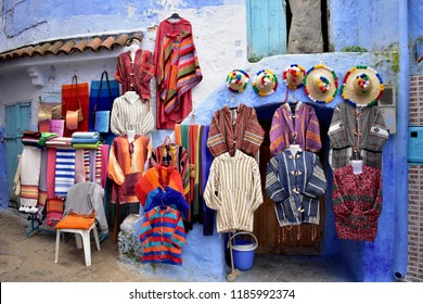 Colourful kaftans for sale displayed against a blue wall at a marketplace in Chefchaouen