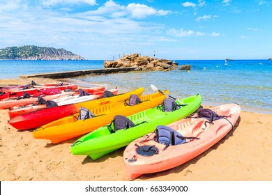 Colourful kayaks on sandy Es Figueral beach, Ibiza island, Spain