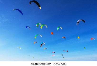 Colourful kites in flight airborne against a blue sky. Kite surfing on the sea.