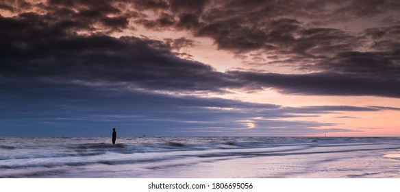 The colourful light reflects on the incoming tide at Crosby beach, silhouetting one of the Iron Men statues in April 2017.  Seen in Liverpool, England.