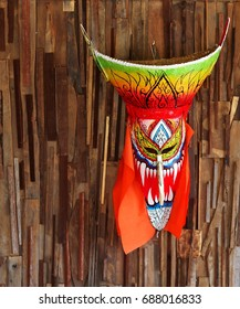 colourful masked ghost monster sculpture figure called PHI-TA-KHON, the folklore folk art mask  used in traditional cultural costume festival LOEI province THAILAND hanging on rough surface wood wall