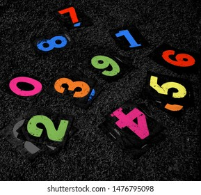 Colourful metallic number plates on a ground