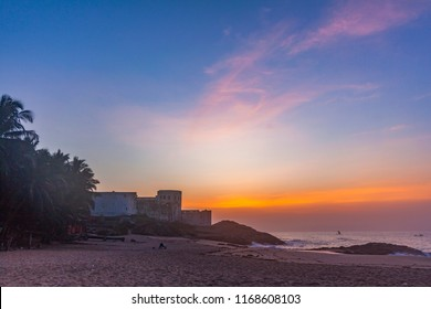 Colourful morning sky on the beach of Cape Coast, Ghana. Sunrise over an old castle and the ocean
