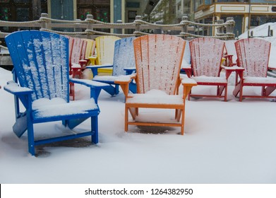 Colourful Muskoka chairs covered in white snow during a winter morning in Ontario, Canada. Buildings are visible in the background.