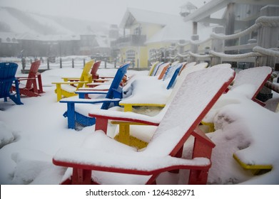 Colourful Muskoka chairs covered in white snow during a winter morning in Ontario, Canada. The landscape in background is foggy. Buildings and ski slopes are visible.
