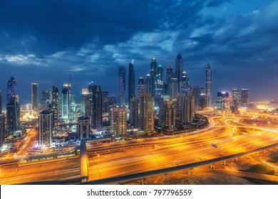 Colourful nightime skyline of a big modern city. Dubai Marina, United Arab Emirates with highways and skyscrapers.