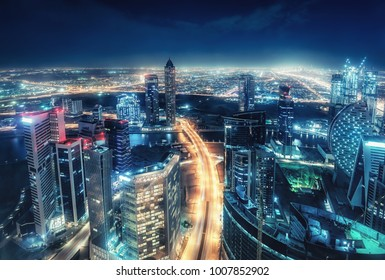 Colourful nighttime skyline of a big modern city. Dubai, United Arab Emirates. Aerial view on highways and skyscrapers.