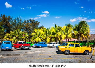 Colourful old American / Russian vintage cars parked near beach in Cienfuegos, Cuba, West Indies, Caribbean, Central America