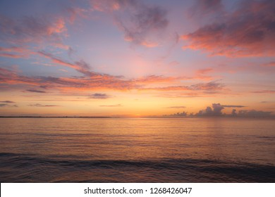 Colourful orange and pink sunset with bright sky and beautiful clouds over Baltic sea.