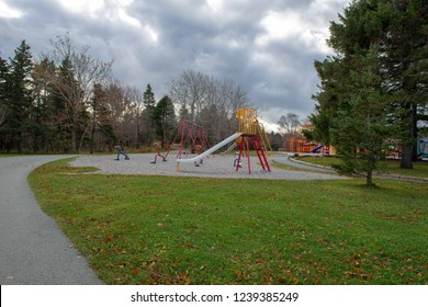 A colourful outdoors children's playground with a slide, swing, seesaw, trees and green grass. It's a cloudy day with trees surrounding the park area. There's gravel and a walkway too.