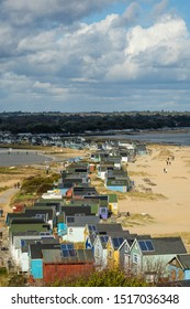 Colourful painted  beach huts at Hengistbury head, Christchurch harbour England with sandy beaches and beautiful sky.