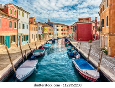 Colourful painted houses along the canal on the island of Burano, Venice, Italy. The island is a popular attraction for tourists due to its picturesque architecture