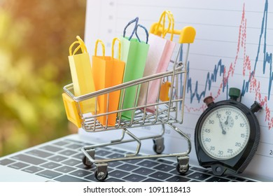 Colourful paper bags in trolley or mini shopping cart and stopwatch on laptop keyboard with chart and nature background. Shop online and e-commerce concept.