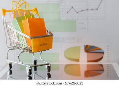 Colourful paper bags in yellow trolley on tablet with chart background. Consumers can buy products directly from seller over internet using web browser. Online shopping and e-commerce concept.