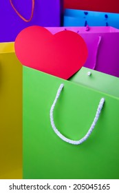 Colourful paper shopping bags with red heart. Yellow, violet, red, blue, pink and green shopping bags.