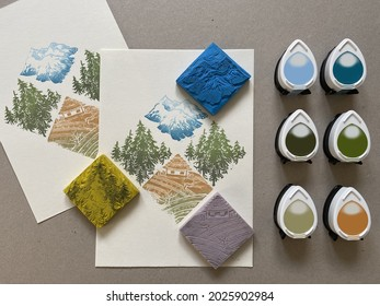 A colourful pattern of mountains, pines and a cottage printed on paper, with the hand-carved rubber stamps, and the green, blue and yellow colored ink pads used for the process.