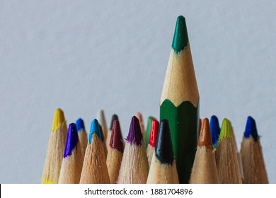Colourful pencils with green sticking out of the others