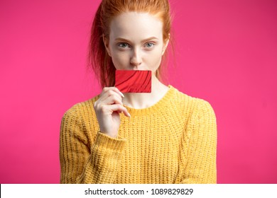 Colourful picrure of Ginger young lovely girl in yellow jersey holding credit card looking at camera.