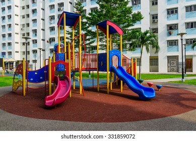 Colourful playground for children in public housing block in Singapore. Surrounded by green trees