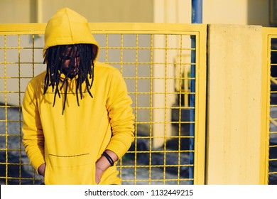 Colourful portrait of young african man wearing dreadlocks and hoody, yellow color lattice fence on background