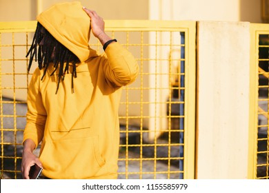 Colourful portrait of young african man wearing dreadlocks and hoody, keep mobile phone. Yellow color lattice fence on background