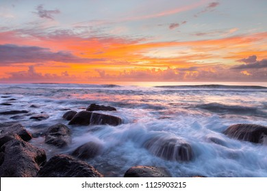Colourful red sunrise with ocean water cascading over rocks at Burleigh Heads Gold Coast