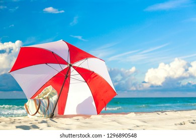 Colourful red and white umbrella with beach bag on the ocean beach against beautiful blue sky and clouds. Relaxation, vacation idyllic background.
