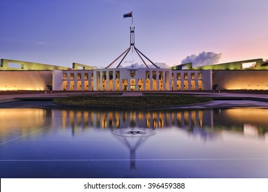 colourful reflection of Canberra's new parliament building in a fountain pond at sunset.