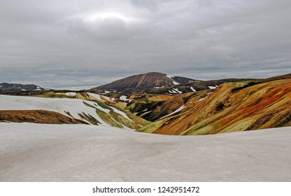 Colourful rhyolite mountains under white snow in summer, Laugavegur hiking trail, Fjallabak Nature Reserve, Highlands of Iceland, Europe