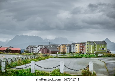 Colourful row of wooden houses on the coast of promenade spit in town of Homer in Alaska during cloudy and rainy day with mountain view and sea coast