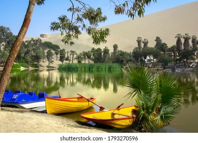 Colourful rowboats moored at Huacachina lagoon, palm trees and sand dunes reflected in the lake, an oasis in the Atacama desert, Ica, Peru, South America