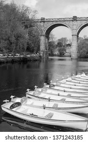 Colourful rowing boats near the railway viaduct on the River Nidd at Knaresborough, North Yorkshire, England.