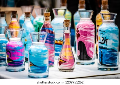 Colourful sand art designs in differently shaped, corked, glass bottles displayed on a table top stall at a craft market