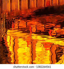 Colourful saturated red and yellow abstract design from reflections in water of the River Cam under the railway bridge in East Chesterton, Cambridge, UK.
