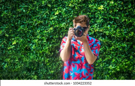 colourful shirt smart photographer capture photo shot with DSLR digital camera on green garden background.